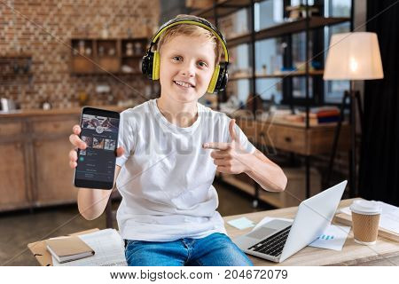 Best application. Cheerful pre-teen boy sitting on the table, listening to the music in headphones and showing his smartphone with a music streaming app open on it