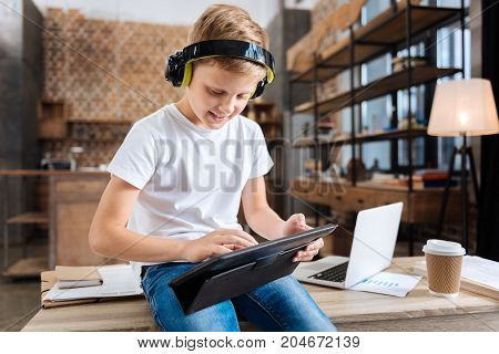 Excited to play. Upbeat lovable boy sitting on the table in the study and playing on his tablet while listening to the game sounds in the headphones