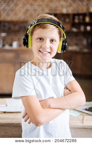 Enjoying music. Joyful pre-teen boy listening to the music in his headphones and posing for the camera while folding his arms