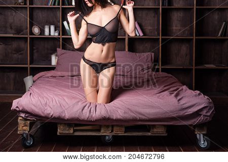 Seductive sexy gorgeous woman wearing lingerie in bed at home. Attractive sensual young girl. Female underwear fashion. Woman relaxing in bed in loft apartment