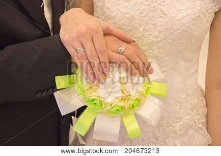 Female and man's hand of newlyweds with silver rings on a bouquet with artificial colors of their silk of green and white color