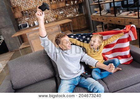 Happy winners. Adorable little boy wrapped in the American flag sitting on the sofa next to his father and celebrating victory in video game together with him