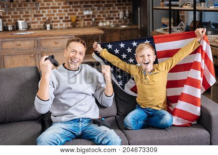 Cheerful celebration. Cheerful pre-teen boy wrapped in the American flag and his upbeat father holding a game controller sitting on the sofa and making gestures of winners