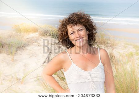 Portrait Of A Beautiful Middle Aged Woman Smiling And Walking On The Beach