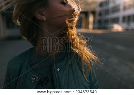 Woman portrait with windy hair in motion closeup. Young independent girl on city street