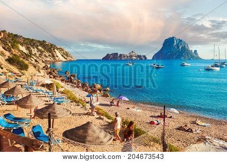 Ibiza Island Spain - June 12 2017: People enjoying the summer at Cala d'Hort beach. Cala d'Hort in summer is extremely popular beach have a fantastic view of the mysterious island of Es Vedra. Ibiza Island Balearic Islands. Spain