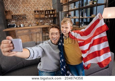Happy state holiday. Cheerful young father sitting on the sofa and taking a selfie with his cute pre-teen son wearing an American flag, celebrating a state holiday