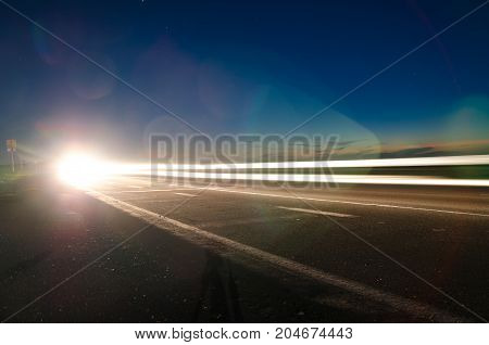 The asphalt road in the countryside at night with the light passing through it at the speed of cars on long exposure
