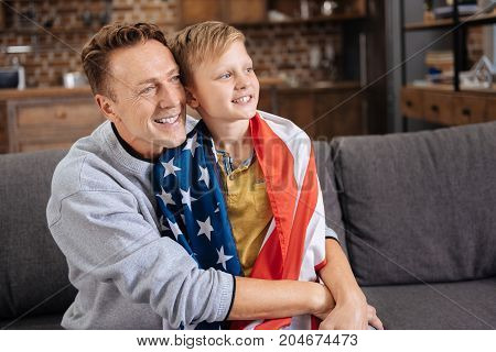 Lovely cuddles. Happy loving father sitting on the sofa and cuddling his beloved little son wearing a US flag on the shoulders