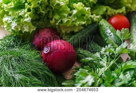 Beautiful green greens with cucumbers and red tomato and red onions.