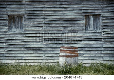 old wooden barrel on the background of a wooden wall. roughly hewn house and old oak barrel.  copy space for your text