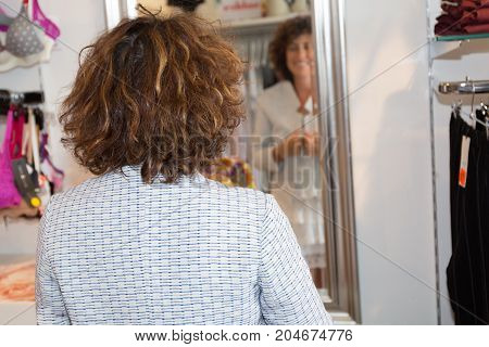 Shopping, Fashion, Style And People Concept - Happy Woman Choosing Clothes And Looking To Mirror In