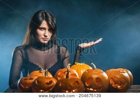 Serious woman with Halloween pumpkins over blue smoky background showing open hand palm with copy space