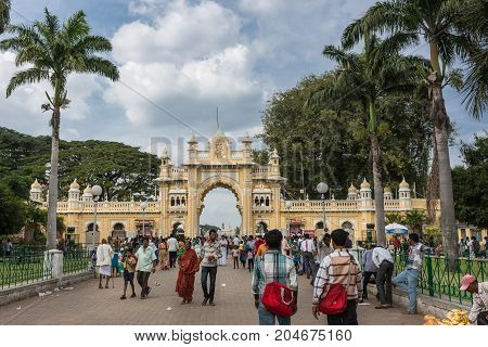 Mysore India - October 27 2013: Yellow South entrance gate to Mysore Palace domain among green trees and under blue sky with white clouds. Many people with colorful clothes in photo.