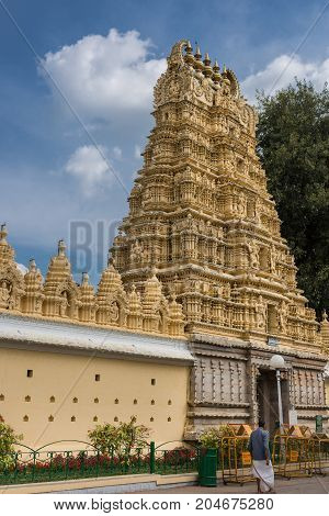 Mysore India - October 27 2013: Yellow Gopuram of Swetha Varaaha Swamy Devastanam temple at Mysore Palace under blue sky with white clouds and one green tree. Entrance tower and part of wall.