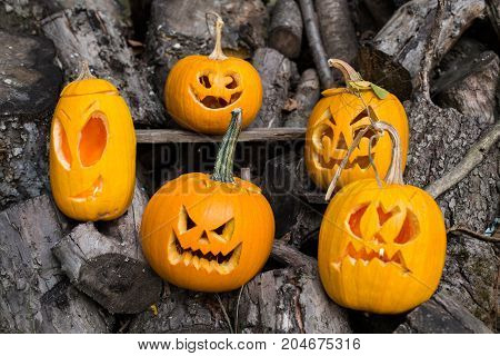 Halloween Themes. Composition Of Five Carved Halloween Pumpkins On Wooden Background. Pumpkins With