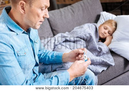 Worried parent. Concerned young father sitting on the sofa next to his ill son covered with blanket and checking his temperature by looking at the medical thermometer poster