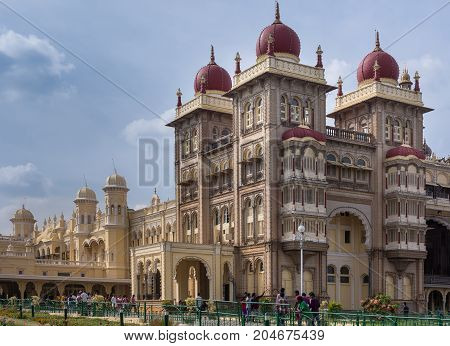Mysore India - October 27 2013: Southeast brownish square tower complex of Mysore Palace with its maroon domes under cloudscape. Many visitors on ground level.