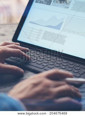Closeup view of male hands typing electronic tablet keyboard-dock station.Man working at the wooden table at office.Vertical, blurred background