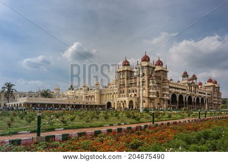 Mysore India - October 27 2013: Wide shot out of garden of South and East facades of Mysore Palace under cloudscape. Yellow building with towers and maroon domes. Flowers up front.