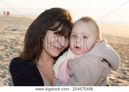 Smiling Mother And Little Daughter On Sea Nature Beach. Happy People Outdoors