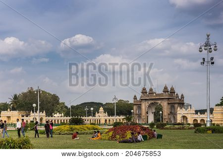 Mysore India - October 27 2013: Brown stone main East Gate to Mysore Palace with yellow side buIldings under cloudscape. Shot from Southwest of garden. Visitors add colors.