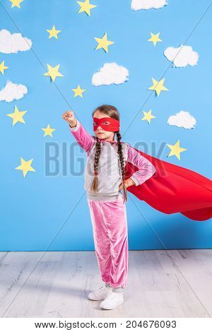 Six year blonde girl dressed like superhero having fun at home. Kid on the background of bright blue wall with white clouds and yellow stars. Girl power concept.
