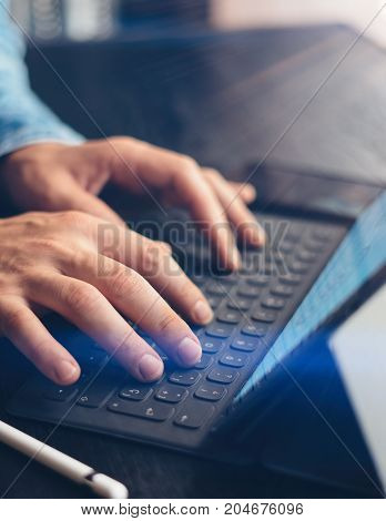 Closeup view of male hands typing on electronic tablet keyboard-dock station. Man working at office.Vertical, sunlight effect.Cropped