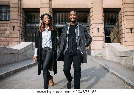 Happy fashionable pedestrians on city street. Smiling black people, African American joyful mood, happiness concept