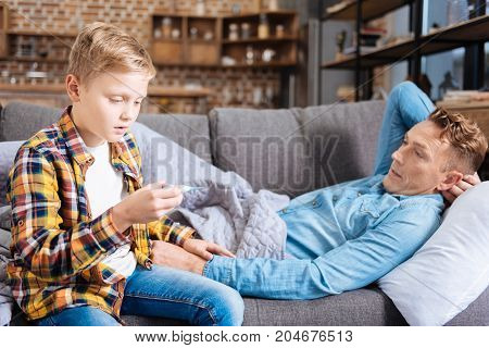 Bad news. Worried pre-teen son sitting at the sofa near his diseased father and checking his temperature while looking concerned about the result