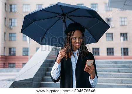 Good news on mobile phone. Moody weather. Happy black female with an umbrella on rainy day, street fashion, happiness concept