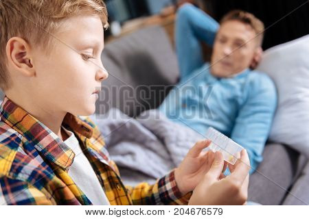 Hard choice. The close up of a worried pre-teen boy holding a pill organizer and choosing necessary medication for his ill father lying on the sofa