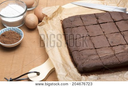 Chocolate brownie bake with flour, eggs, coco powder and a knife