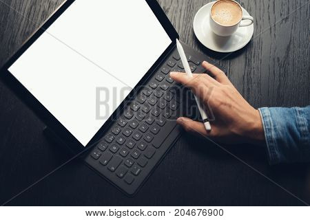 Man using tablet and typing on electronic tablet keyboard-dock station while sitting at wooden table.White blank device screen.Blurred background.Horizontal mockup