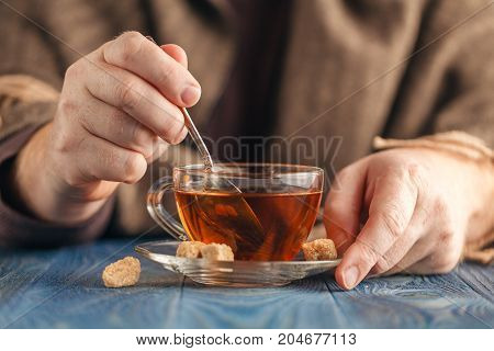 Dunking sugar in hot tea in glass cup