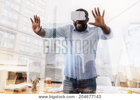 Enjoying life. Waist up of happy young African American wearing virtual glasses while standing in and putting his palms forward