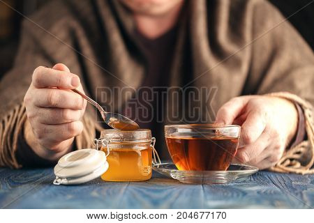 Man in sweater drink hot tea with honey