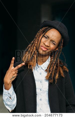 Victory gesture. Confident young black lady outdoors. Happy African American woman in selective focus, stylish model posing on dark background, happiness concept