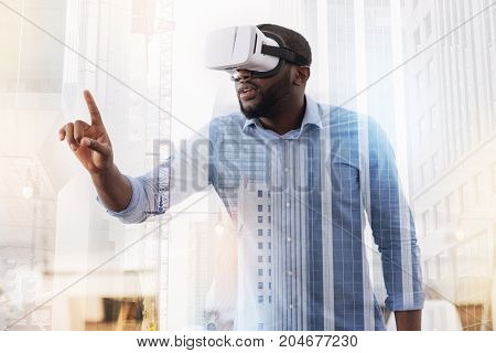Real magic. Waist up of young African American wearing virtual glasses and being concentrated while putting his finger forward