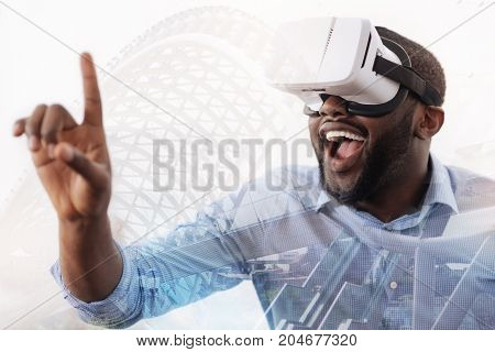 Bright emotions. Close up of young excited African American looking at his finger through virtual glasses and expressing astonishment