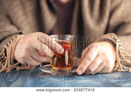 Male add sugar in hot tea on table