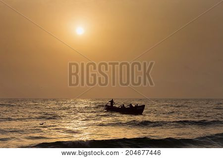 Fishermen silhouettes on a boat, at sunrise