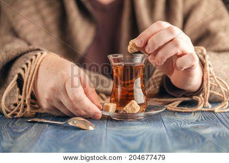Man hands Dunking sugar in hot tea