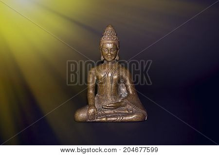 Buddhist meditation. Traditional bronze buddha meditating in rays of divine light. Zen buddhism and spiritual enlightenment or awakening. New Age image with copy space.