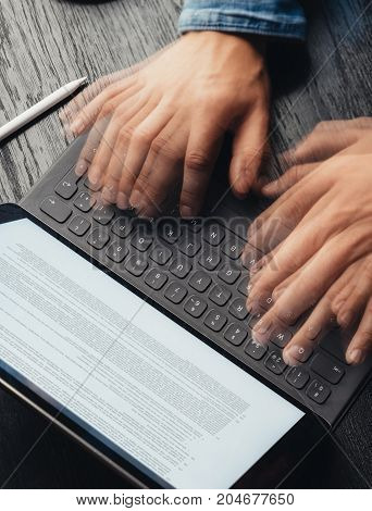 Closeup view of male hands quickly typing on electronic tablet keyboard-dock station. text information on device screen. Man working at office.Vertical, top view
