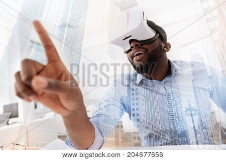 Just imagine. Close up of young curious man wearing virtual glasses while putting forward his finger and expressing interest