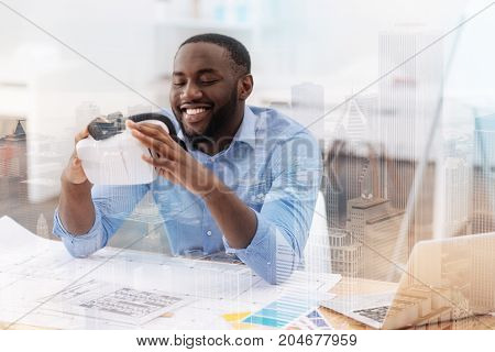 Funny device. Young cheerful African American holding virtual glasses with both hands while sitting at the table and expressing interest
