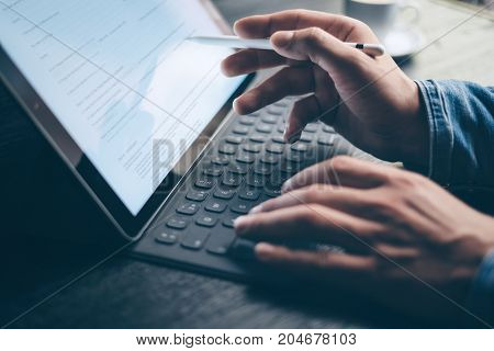 Man working at office.Male hands typing on electronic tablet keyboard-dock station.Business text information on device screen. Horizontal, cropped