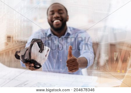 High quality device. Satisfied young African American keeping virtual mask in right hand while raising his thumb up