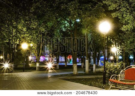 An empty city steet at night. Walkway illuminated with the lanterns. The town of Pokrov, Ukraine